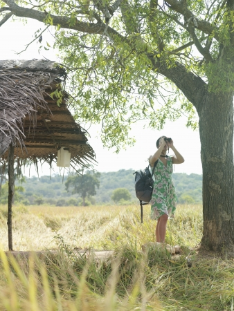 thatched roof: Young woman looking through binoculars by thatched roof