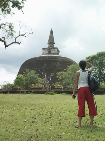 sight seeing: Young woman looking at stupa back view
