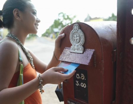 mixed race woman: Young woman putting postcard to mailbox smiling LANG_EVOIMAGES
