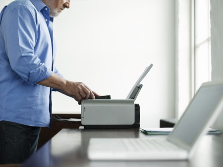 office equipment: Middle-aged man using printer side view mid section LANG_EVOIMAGES