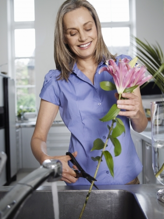 rinsing: Mid-adult woman rinsing and cutting flowers in kitchen sink LANG_EVOIMAGES