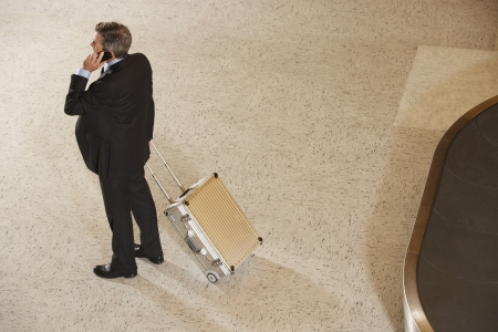 businessman standing: Business man using mobile phone by baggage claim in airport LANG_EVOIMAGES
