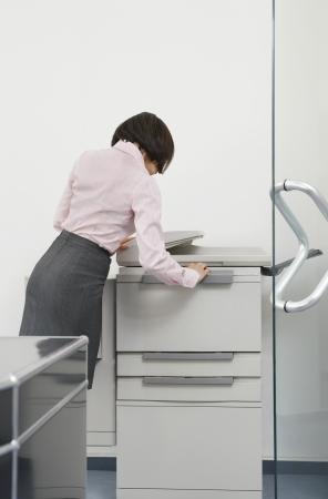 fotocopiadora: Mujer que usa fotocopiadora en la oficina