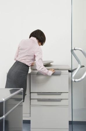photocopier: Woman using photocopier in office