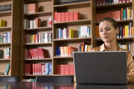 writing activity: Young woman using laptop in library