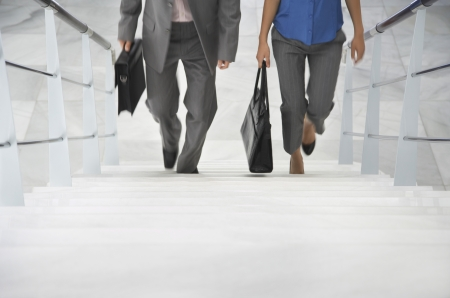 woman stairs: Two business people walking up stairs