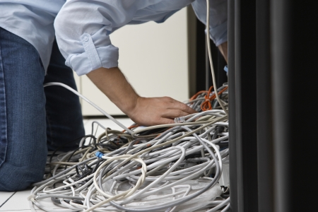 Man working on tangle of computer wires in office Stock Photo - 19076914