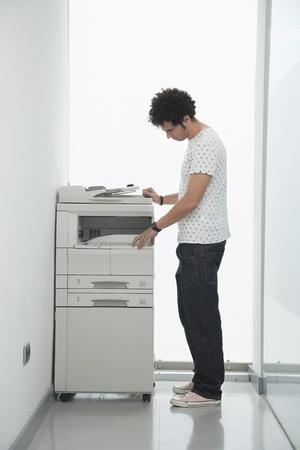 Man using copy machine in hallway