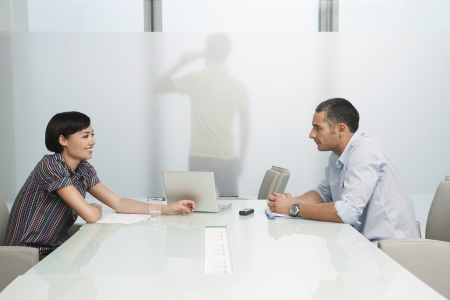 two people with others: Man and woman talk over conference table man on mobile phone visible through translucent office wall