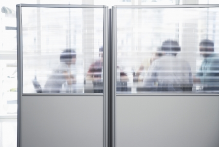 unknown age: Office workers meeting behind cubicle wall in office