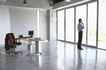 trabajador oficina: Hombre mirando por la ventana en el edificio de oficinas vac�o