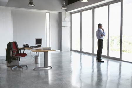 man office: Man looking out of window in empty office building