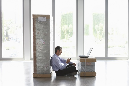 empty: Man using mobile phone and laptop between packages in empty office