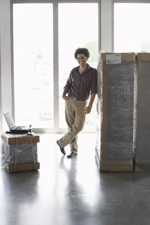 Young man standing by packages in empty office Stock Photo - 19076987