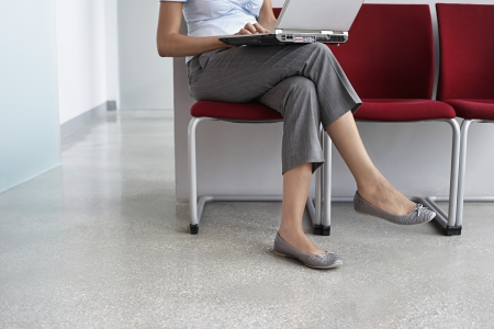 legs crossed at knee: Woman using laptop on chairs in corridor low section
