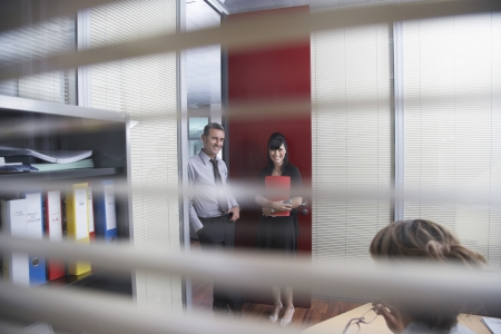 two people with others: Business colleagues talking in office seen through window blinds
