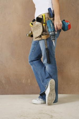 low section: Woman with toolbelt and drill leaning against wall low section