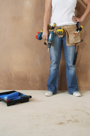 toolbelt: Woman with toolbelt and drill leaning against wall low section