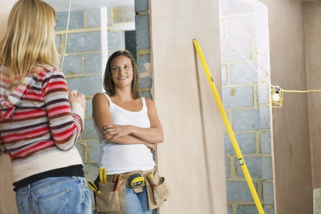 toolbelt: Woman with toolbelt leaning against wall taling to friend