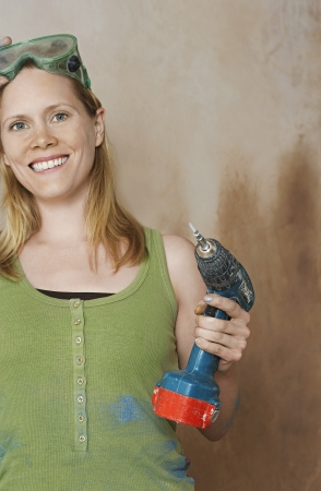 power drill: Woman with protective goggles holding power drill portrait LANG_EVOIMAGES