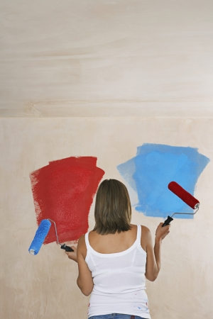 ble: Woman facing wall painted on ble and red holding with paint rollers back view