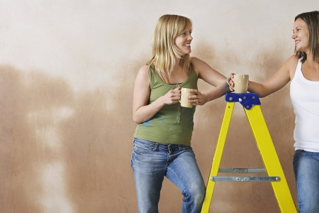 step ladder: Two women leaning on step ladder holding mugs
