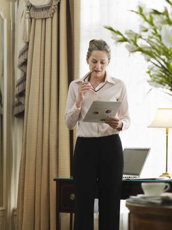 lap of luxury: Business woman reading document in home office LANG_EVOIMAGES