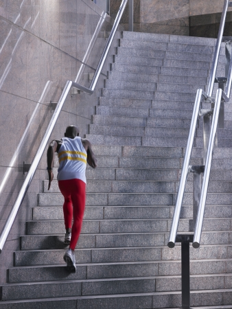one adult only: Male athlete running up staircase outside building