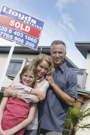 Parents and daughter (7-9) embracing outside new home portrait Stock Photo - 19077318