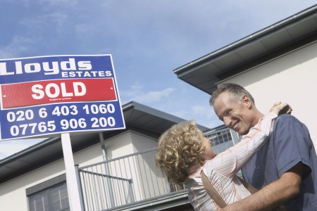 Couple embracing outside new home with sold sign Stock Photo - 19077320
