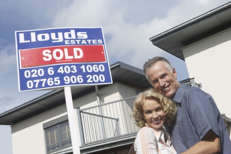 Couple embracing outside new home with sold sign portrait Stock Photo - 19077321