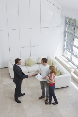 real estate agent: Real estate agent with couple in new home man shaking hand elevated view LANG_EVOIMAGES