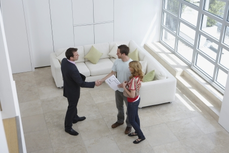 real estate house: Real estate agent with couple in new home man shaking hand elevated view LANG_EVOIMAGES