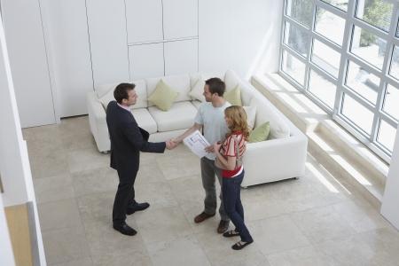 Makelaar met een paar in het nieuwe huis man schudden hand opgeheven mening