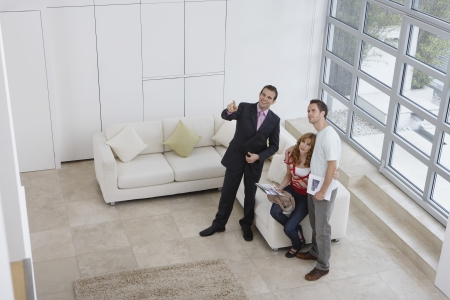 real estate agent: Real estate agent showing couple new home elevated view