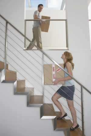upstairs: Couple carrying boxes upstairs in new home