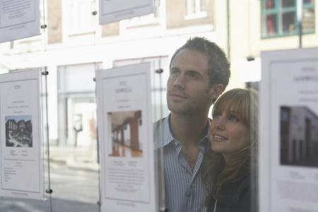 Paar sucht durch das Fenster an Immobilienmakler Standard-Bild