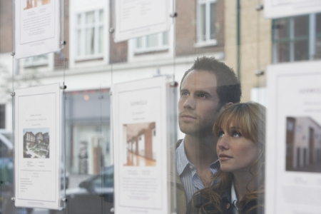 looking through window: Couple looking through window at estate agents