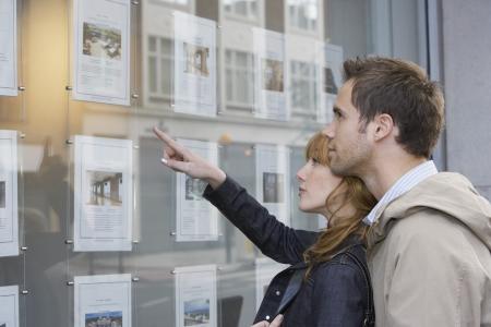 Paar sucht in Fenster außerhalb Immobilienmaklern Standard-Bild