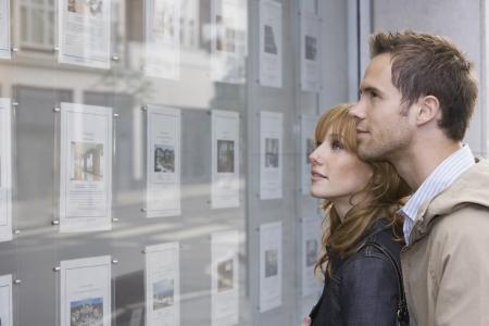 Paar sucht in Fenster außerhalb Immobilienmaklern