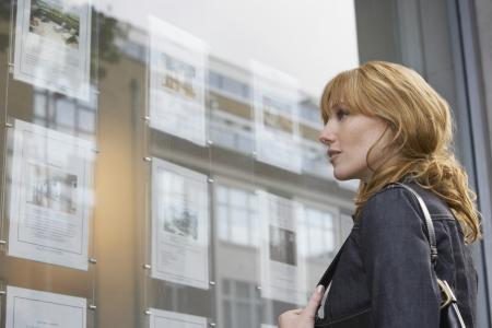 Frau in Fenster außerhalb Immobilienmaklern