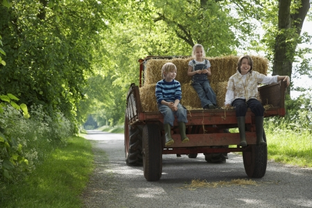 road tractor: Three children (5-9) sitting on trailer on country lane