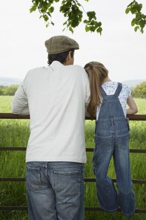 padre e hija: Padre e hija (5-6) que se coloca en la cerca en el campo LANG_EVOIMAGES