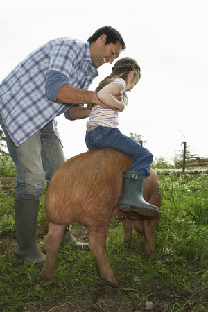 sty: Father helping daughter (5-6) to ride pig in sty