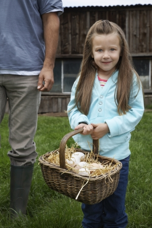 one person with others: Girl (5-6) holding egg basket father (low section) standing nearby outdoors portrait