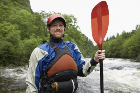 oar: Man holding kayak oar by river portrait LANG_EVOIMAGES