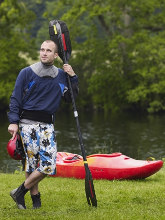 personal watercraft: Man with kayak paddle by river