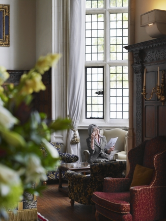 muebles antiguos: Mujer de mediana edad sentado y leyendo en el interior con muebles antiguos LANG_EVOIMAGES