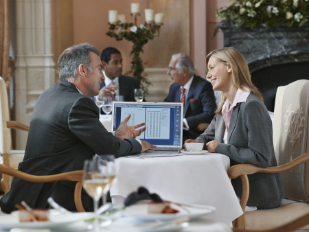 two people with others: Two business people having conversation at restaurant table with laptop