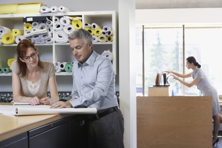 two people with others: Man and woman studying paperwork in office
